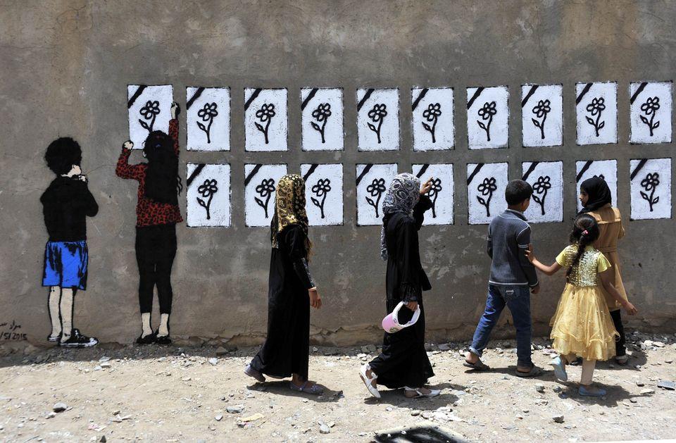 People pass by Murad Subay's mural