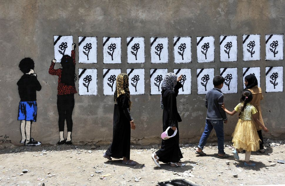 "People pass by Murad Subay's mural ""Flowers Bouquet"" in Sanaa in May 2015. The Yemeni street artist has spent five years maki"
