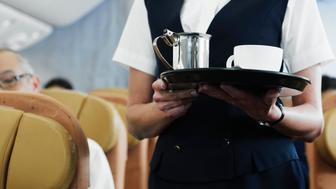 Flight attendant holding tray with coffee, mid section