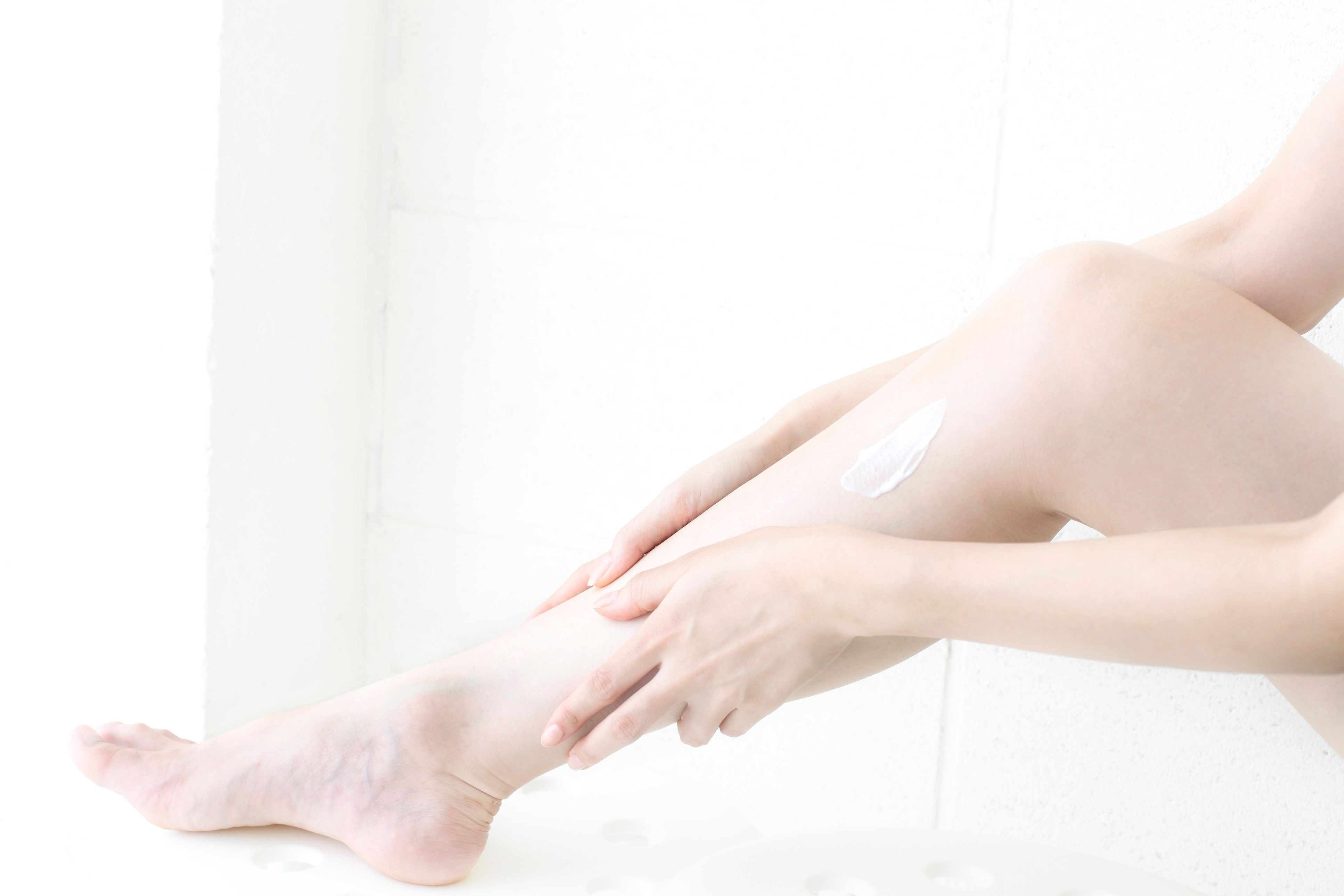 young woman applying a body cream to foot