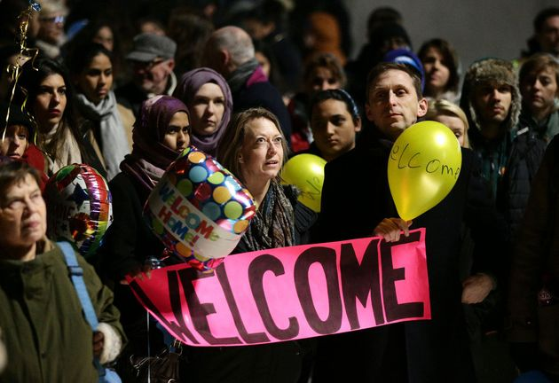 A group of Brits wait at King's Cross Station in London to welcome Syrian refugees to the