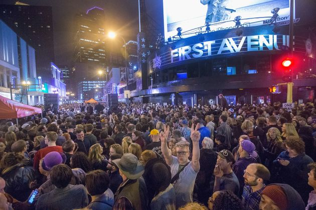 People listen to Prince music during a memorial street party outside the First Avenue