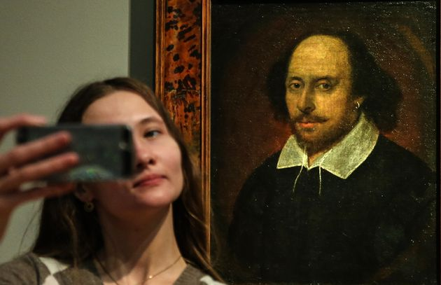 A woman takes a selfie in front of a portrait of William Shakespeare on April 21, 2016 in Moscow. April...