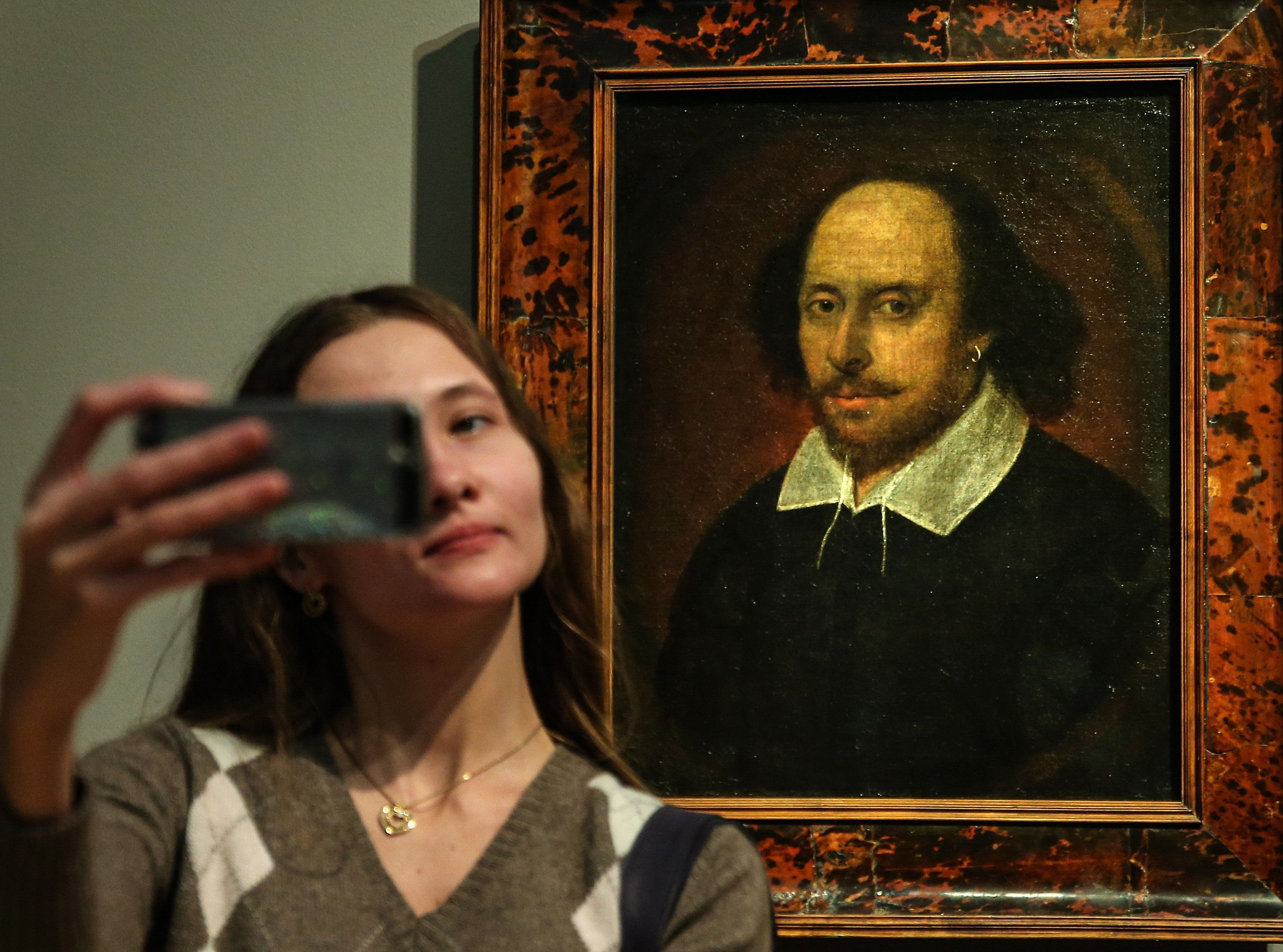 A woman takes a selfie in front of a portrait of William Shakespeare on April 21, 2016 in Moscow. April 23 is the 400th anniv