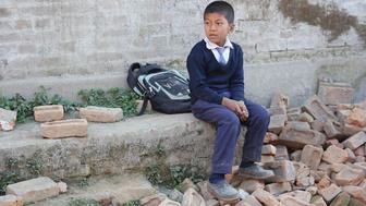 Boy sits in rubble of school in Bhaktapur