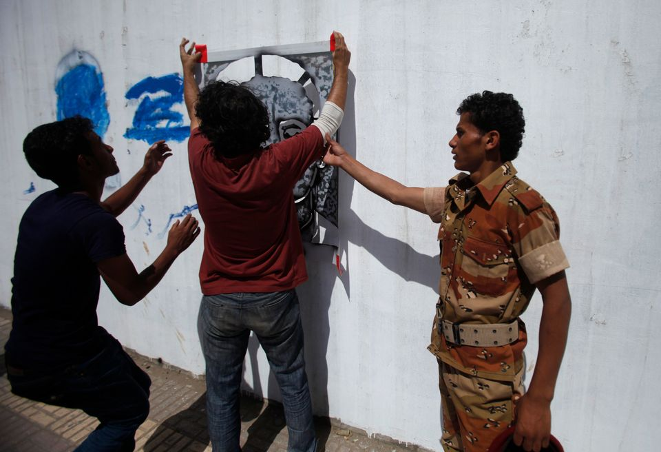 The campaign drew the attention of the authorities. Above, a soldier tries to stop Subay painting a portrait...
