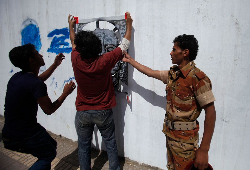 The campaign drew the attention of the authorities. Above, a soldier tries to stop Subay painting a portrait of one of the di