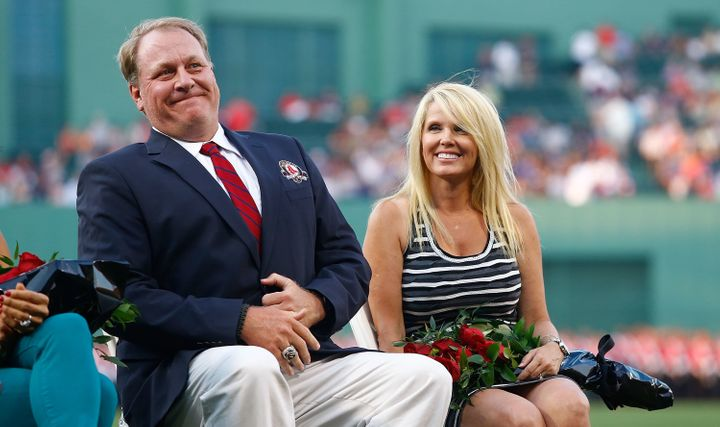 Former Boston Red Sox pitcher Curt Schilling sits with his wife, Shonda Schilling, while being inducted into the Red Sox Hall