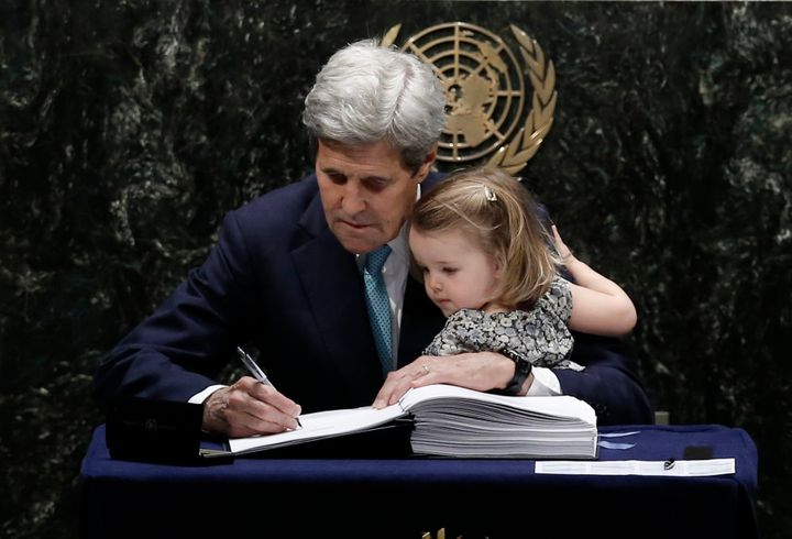 U.S. Secretary of State John Kerry holds his 2-year-old granddaughter as he signs the Paris agreement on climate change, Apri