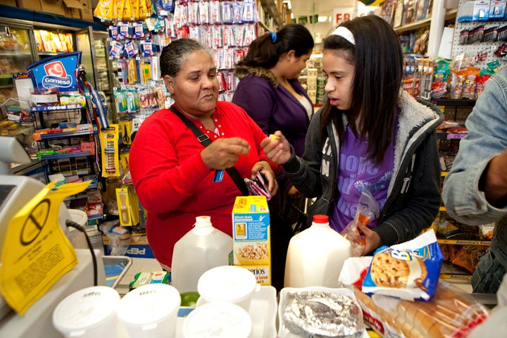 Carmen Munoz and Leidy Maldonado use a SNAP card at Tesoro Supermarket. About one in eight Americans now use the program, als