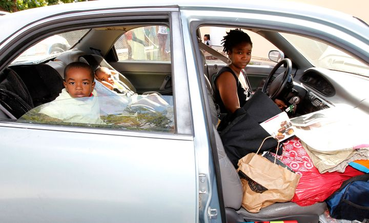 Debbie Summers and her children sit in her car, with all of their possessions, as they wait for admittance to a homeless shel