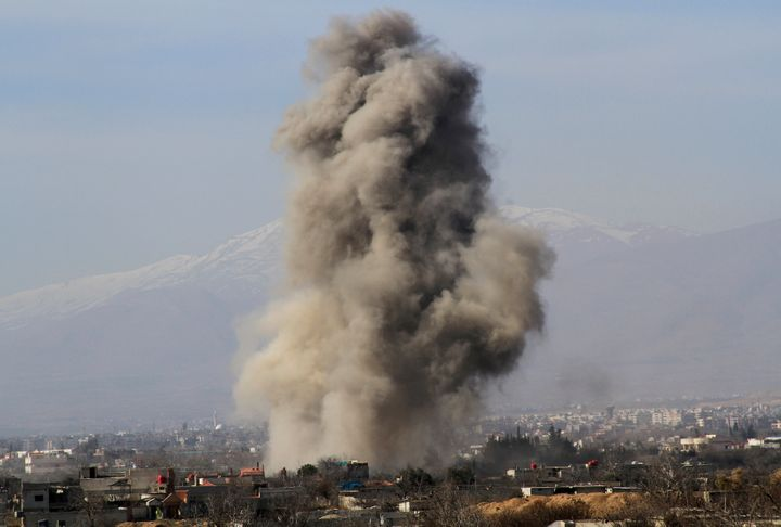 """Smoke rises in Daraya. """"We didn't even look back to see what happened to our home,"""" Haboub recalls."""