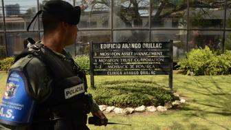 TOPSHOT - A policeman stands guard outside Mossack Fonseca headquarters as members of the Construction Workers Union demonstrate, at Panama city on April 13, 2016.  Police on Tuesday raided the headquarters of the Panamanian law firm whose leaked Panama Papers revealed how the world's wealthy and powerful used offshore companies to stash assets. / AFP / Ed Grimaldo        (Photo credit should read ED GRIMALDO/AFP/Getty Images)