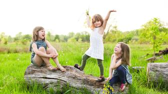 Three little sisters, laughing at the youngest, who but nature, is the funniest.