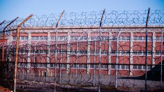 Barbed wire fences surround a building on Rikers Island Correctional Facility in New York December 24, 2013. REUTERS/Lucas Jackson (UNITED STATES - Tags: CRIME LAW)