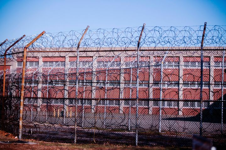 Barbed wire fence surrounds a building at new York's Rikers Island Correctional Facility in 2013.