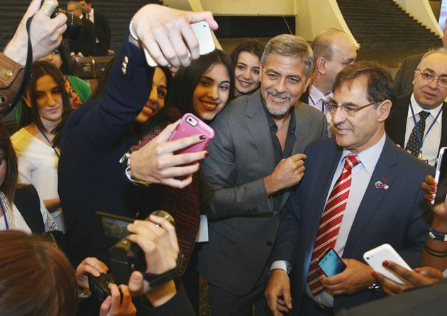 George Clooney stops to pose for selfies before participating in a panel discussion at theSecond...