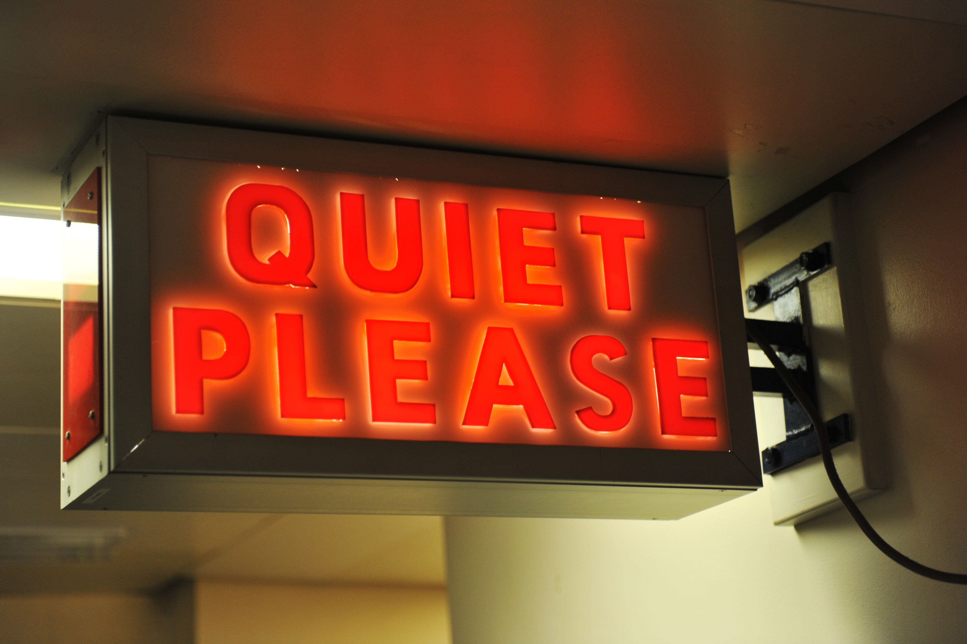 A vintage illuminated sign calling for quiet