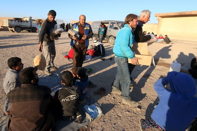 Volunteers from a Kurdish relief organization distribute food to displaced people, who are fleeing violence...