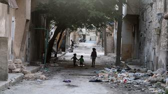 Children walk near garbage in al-Jazmati neighbourhood of Aleppo, Syria April 22, 2016. REUTERS/Abdalrhman Ismail