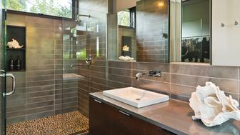 Modern master bathroom with glass door shower and metal style tile with custom features