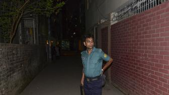 A Bangladeshi police official stands in front of an apartment in Dhaka on April 25, 2016. where here a leading gay rights activist was allegedly hacked to death.  Two people including a leading gay rights activist were hacked to death at an apartment in the Bangladesh capital Dhaka, police said, the latest in a series of attacks on minorities in the Muslim-majority nation. / AFP / MUNIR UZ ZAMAN        (Photo credit should read MUNIR UZ ZAMAN/AFP/Getty Images)