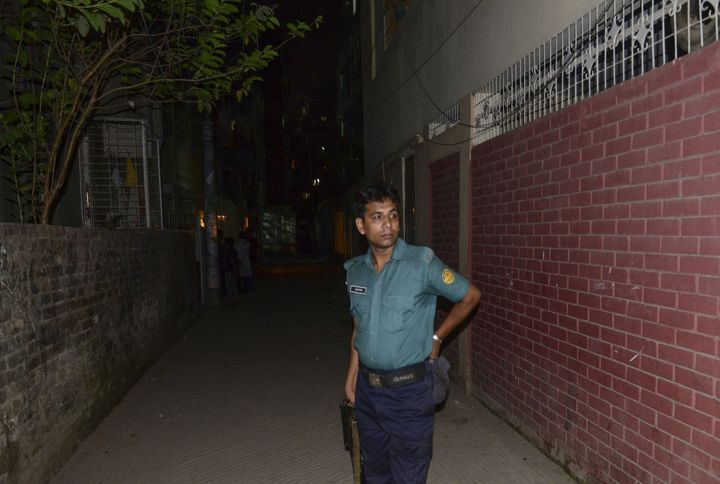 A Bangladeshi police official stands in front of the apartment in Dhaka where Xulhaz Mannan was killed.