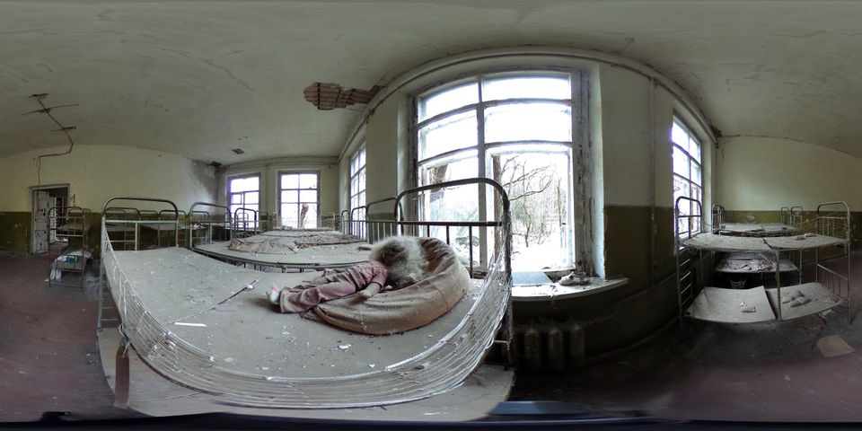 A blackened doll lies on a bed in an abandoned