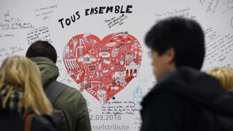 People read messages on a commemorative wall at the Maelbeek - Maalbeek metro station on its re-opening day on April 25, 2016 in Brussels, after being closed since the 22 March attacks in the Belgian capital.  Maelbeek - Maalbeek metro station was hit by one of the three Islamic State suicide bombers who struck Brussels airport and metro on March 22, killing 32 people and injuring hundreds. / AFP / JOHN THYS        (Photo credit should read JOHN THYS/AFP/Getty Images)