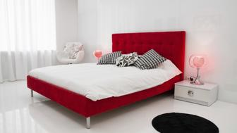 Clean white room with a big red bed and a little round black carpet