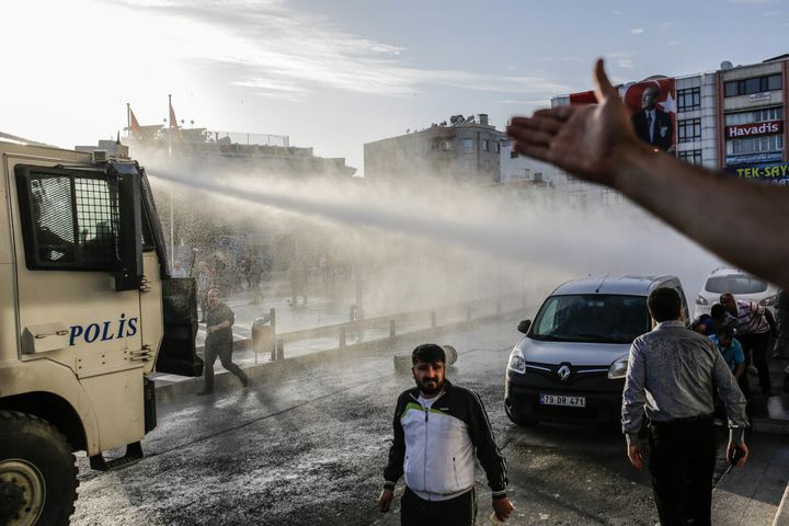 Turkish anti-riot police use water cannon to disperse people who gathered after a rocket hit a mosque on April 24 in Kilis, T