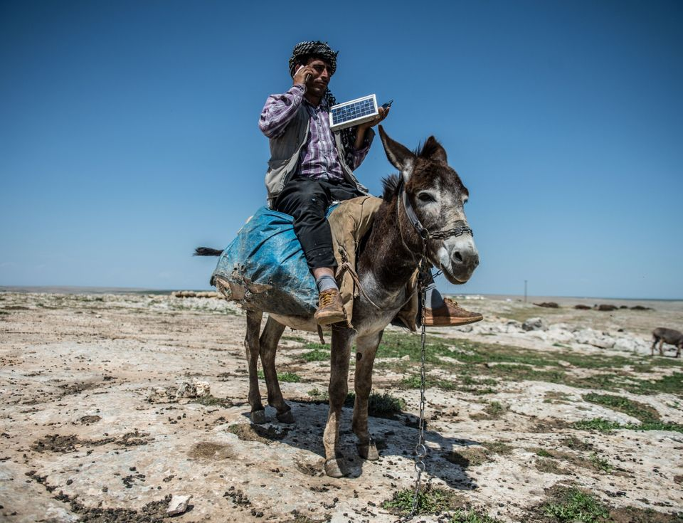 A shepherd in Sanliurfa, Turkey, talks on his phone, which is charged with solar panels carried by a donkey.