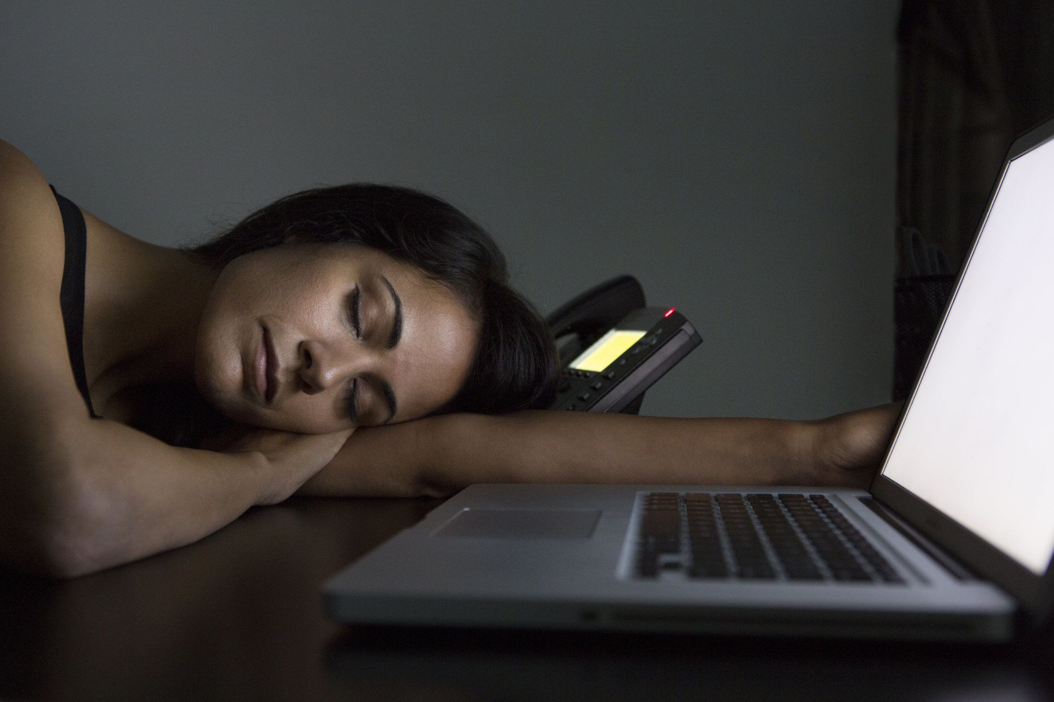 Businesswoman sleeping at desk at night