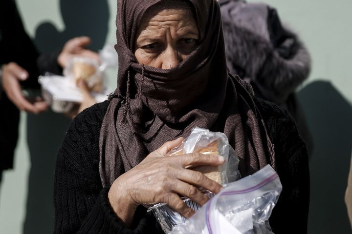 A migrant receives a portion of food and water during food distribution at a relocation camp in Schisto, near Athens, Greece,