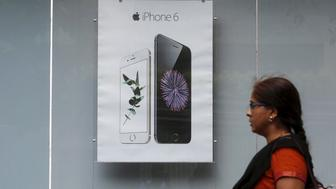 A pedestrian walks past an Apple iPhone 6 advertisement at an electronics store in Mumbai, India, July 24, 2015. With only a tiny share of the world's fastest-growing major smartphone market, Apple Inc is stepping up its push into India, with a first targeted TV advertising campaign, expanded retail network and promotional financing schemes. REUTERS/Shailesh Andrade