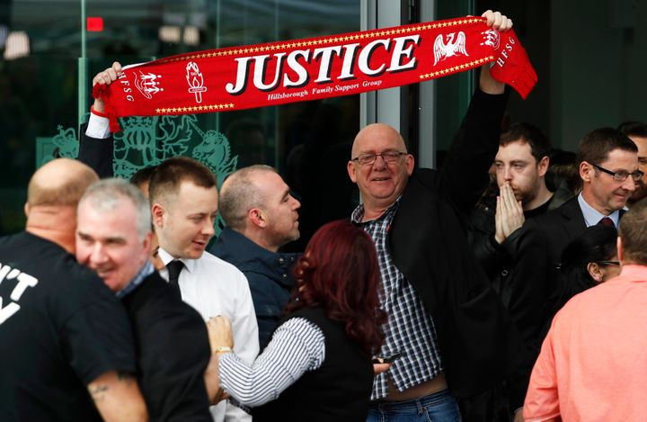 Relatives hold up a scarf after the jury delivered its verdict at the new inquests into the Hillsborough disaster, in Warring