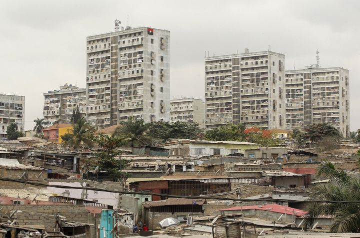 High-rise buildings are seen behind informal settlements in Luanda, Angola, where a yellow fever outbreak has health experts worried.