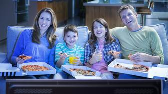 Family eating pizza in front of television in living room