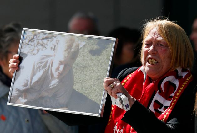 A relative holds up a photo of Keith McGrath, who died in the