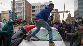 Demonstrators destroy the windshield of a Baltimore Police car as they protest the death Freddie Gray, an African American man who died of spinal cord injuries in police custody, in Baltimore, Maryland, April 25, 2015. Protesters returned to Baltimore's streets Saturday to vent outrage over the death of Gray on April 12.      AFP PHOTO/JIM WATSON / AFP / JIM WATSON        (Photo credit should read JIM WATSON/AFP/Getty Images)