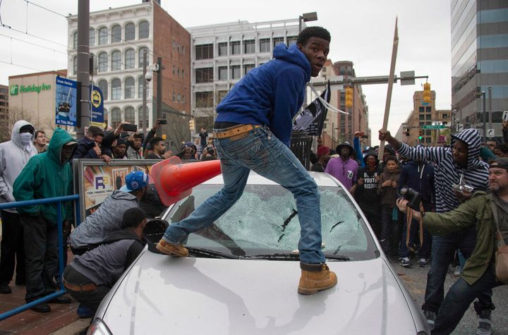 Allen Bullock looks back at the camera as demonstrators destroy the windshield of a Baltimore Police car on April 2