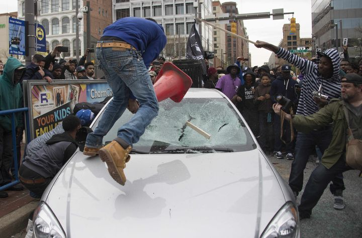 Bullock and other demonstrators smash a Baltimore Police car as they protest the death of Freddie Gray.