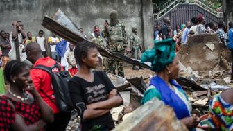 A soldier takes photos while women look at the remains of a house that was burnt down during communal violence ahead of elections in the Taouyah neighbourhood of Guinea's capital Conakry September 25, 2013. Parliamentary elections in Guinea on Saturday officially cap the mineral-rich West African country's return to civilian rule after a 2008 coup, but many fear that the vote could reignite violence that killed dozens of people earlier this year. The contest, two years overdue, is ostensibly for the 114 seats to Guinea's National Assembly, but with no single party expected to command an outright majority, political deal-making is sure to follow. Picture taken September 25, 2013.  REUTERS/Tommy Trenchard (GUINEA - Tags: POLITICS ELECTIONS MILITARY)