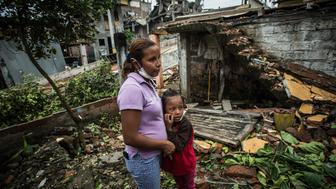 A woman and her daughter visit with neighbors in an area severely damaged by an earthquake in Pedernales, Ecuador, on Friday, April 22, 2016. World leaders from the Vatican to Washington offered support to Ecuador as casualties mounted following one of the strongest earthquakes to strike the South American country in decades. Photographer: Meridith Kohut/Bloomberg via Getty Images