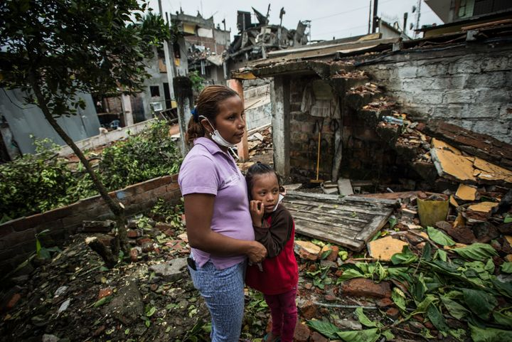 A woman and her daughter visit with neighbors in an area severely damaged by an earthquake in Pedernales, Ecuador.