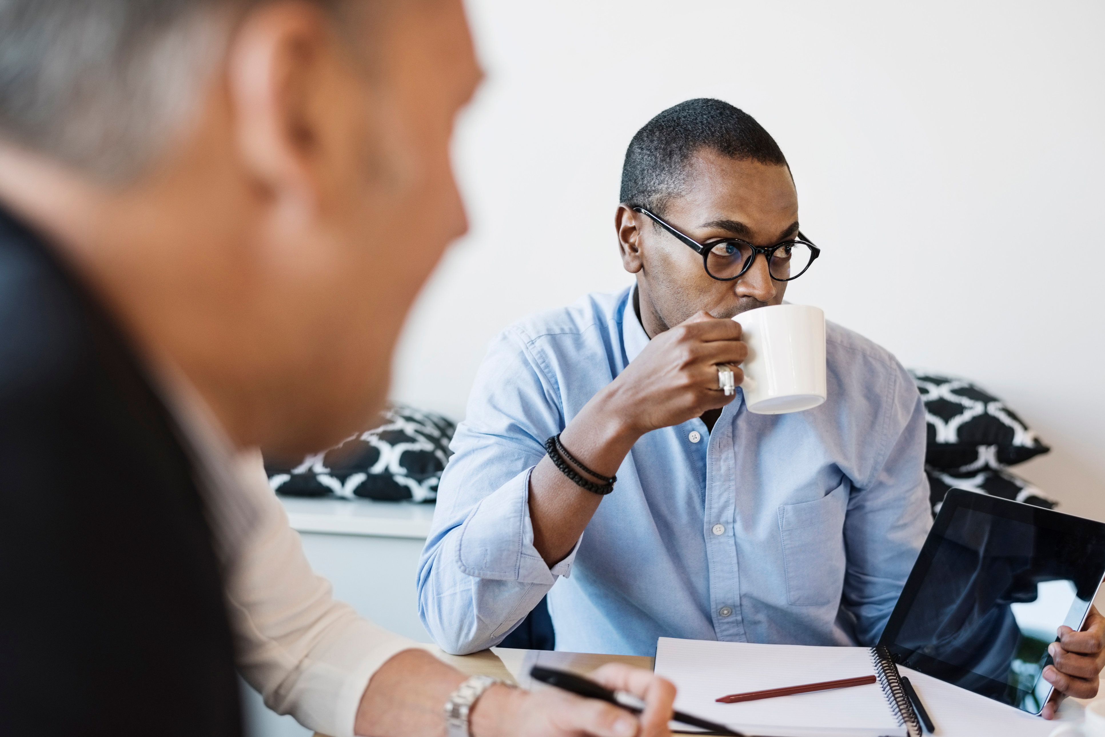Businessman drinking coffee during meeting at office