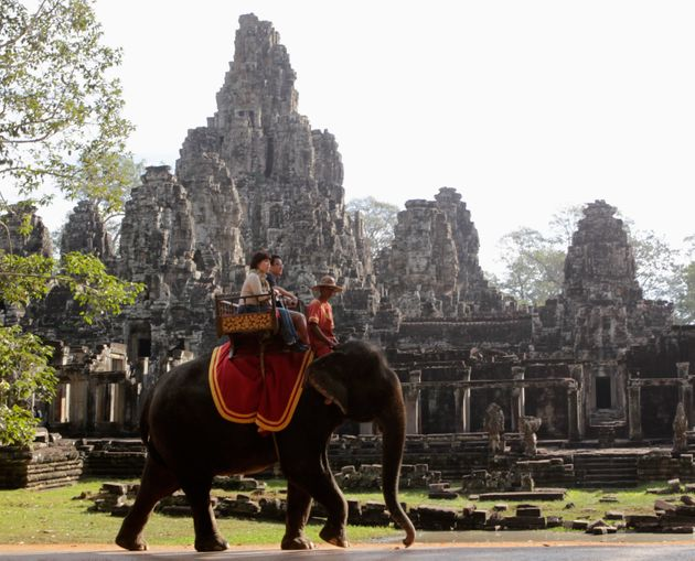 Tourists ride an elephant past the ruins of Cambodia's Bayon temple in Siem Reap, December 22,