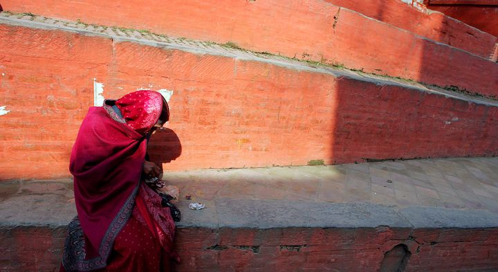 A woman sits at the steps of a Hindu temple in Kathmandu February 5, 2005.