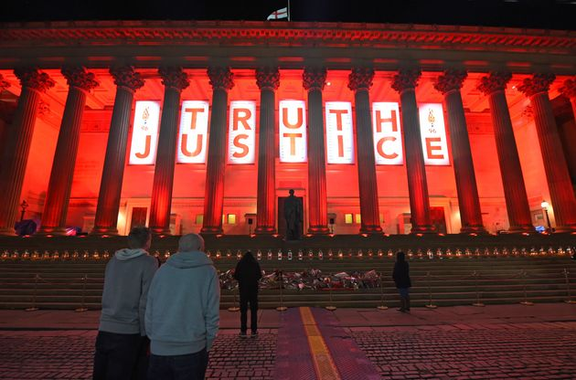 Liverpool's St Georges Hall is lit up Red adorned with a banner reading 'Truth and