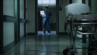 Doctor reading medical chart in hospital corridor